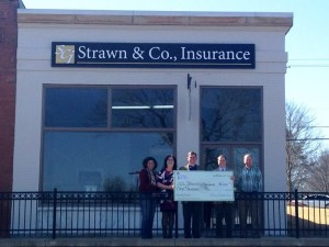 Strawn & Co agents pose with check for facade grant program in front of the strawn & co office