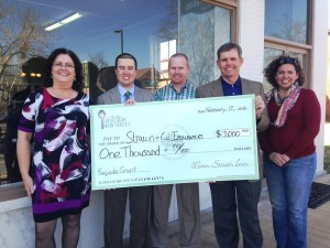 Strawn & Co agents pose with check for facade grant program