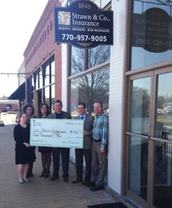 Strawn & Co agents pose with check for facade grant program in front of the strawn & Co office sign