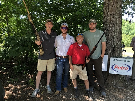 Group of four men holding rifles posing in front of some trees