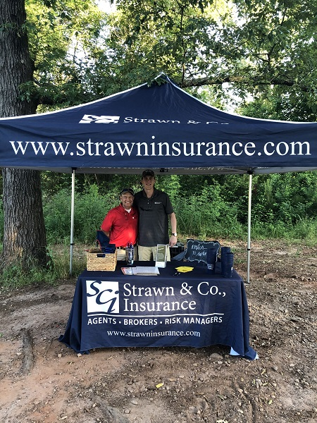 Two agents at the Strawn & Co tent at the Flint River Council Boy Scouts of America Sporting Clay Tournament