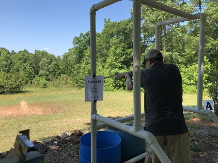 Man holds rifle at his station for the sporting clay tournament