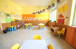 Empty daycare classroom with several tables with yellow chairs