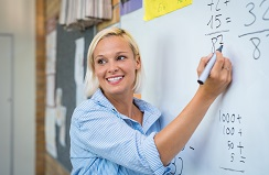 Blonde woman stands at the whiteboard writing numbers